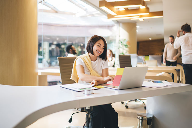 Digital professional woman working on laptop in a shared workspace