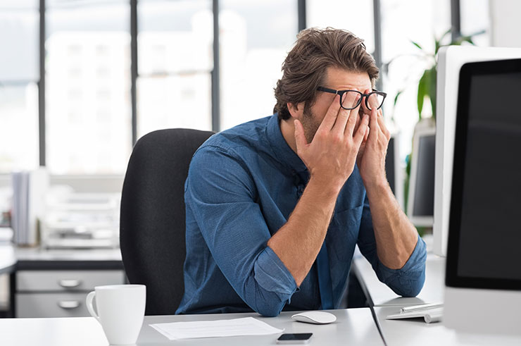 Stressed young businessman covering his face at his desk