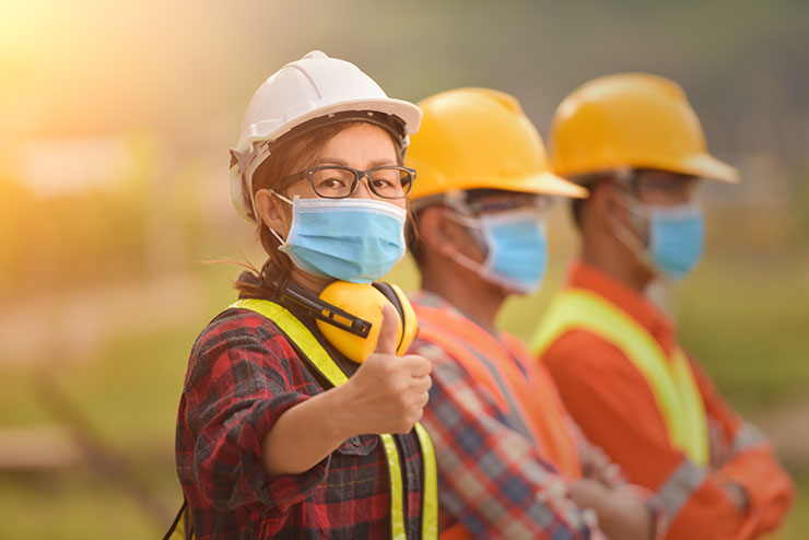 Woman wearing PPE gives thumbs up in warehouse