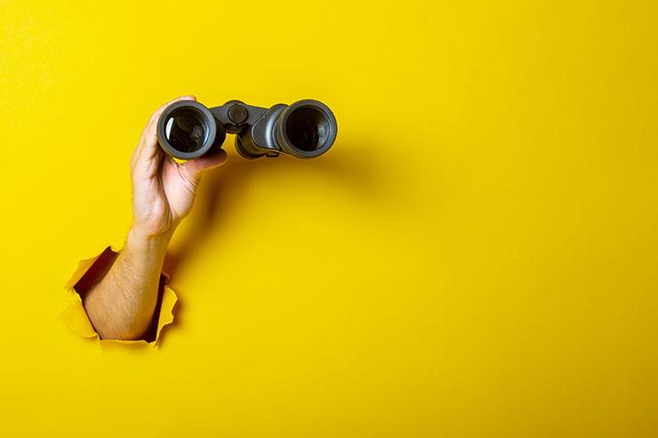 Arm holding binoculars against yellow wall