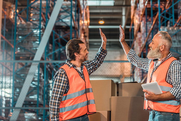 Two warehouse workers high fiving