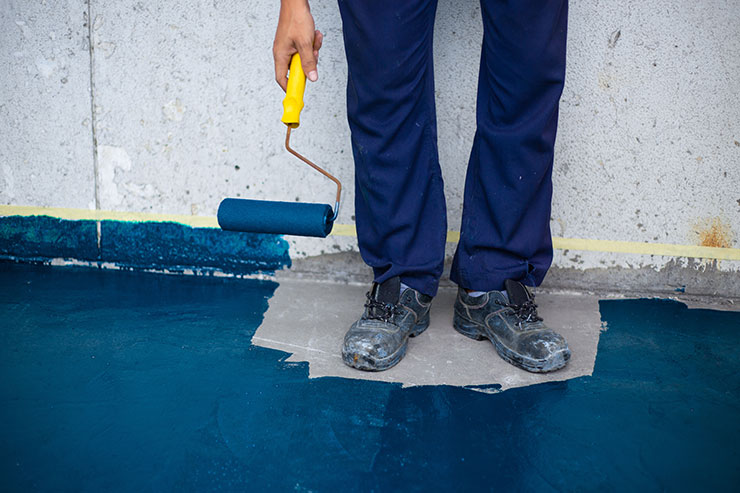 Person holding paint roller has painted floor around their own feet: mistakes made at work