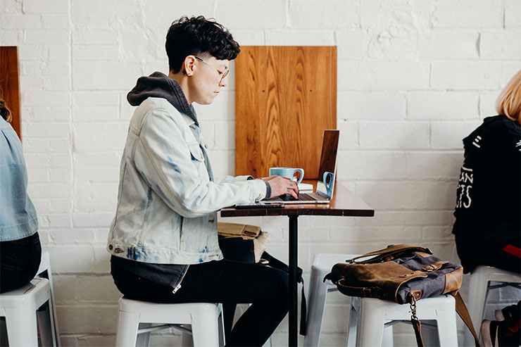 Person on laptop at outdoor café: changes to recruitment and hiring after COVID-19