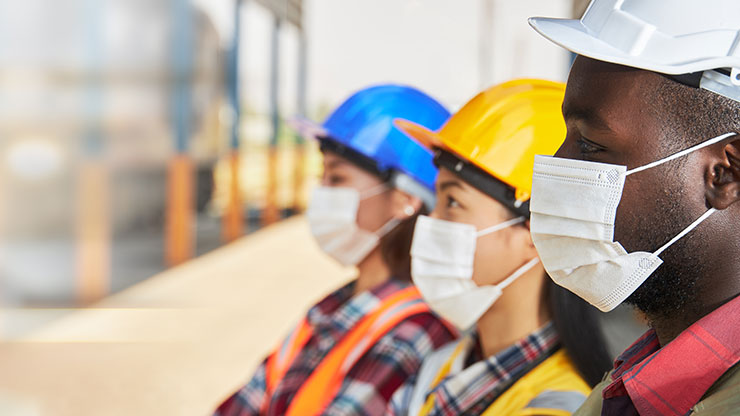 Three people in safety gear stand side by side.