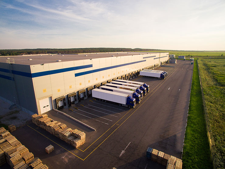 The Pros of Hiring Temporary Employees: distribution warehouse with trucks