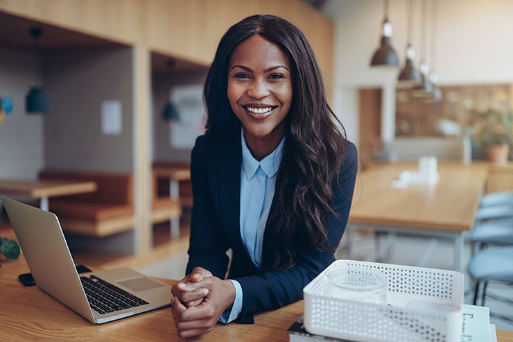LinkedIn personal branding: Smiling woman in suit sitting at laptop
